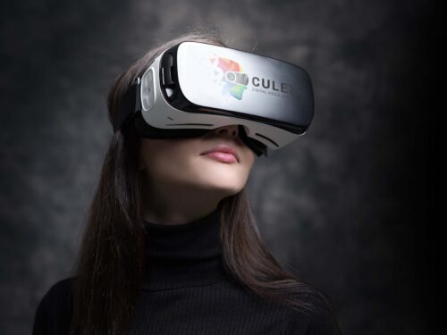 Young woman wearing VR glasses and interacting with virtual reality, entertainment and innovative technology concept